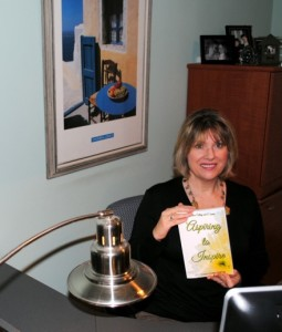 Connie in her writing area holding her copy of Aspiring to Inspire.